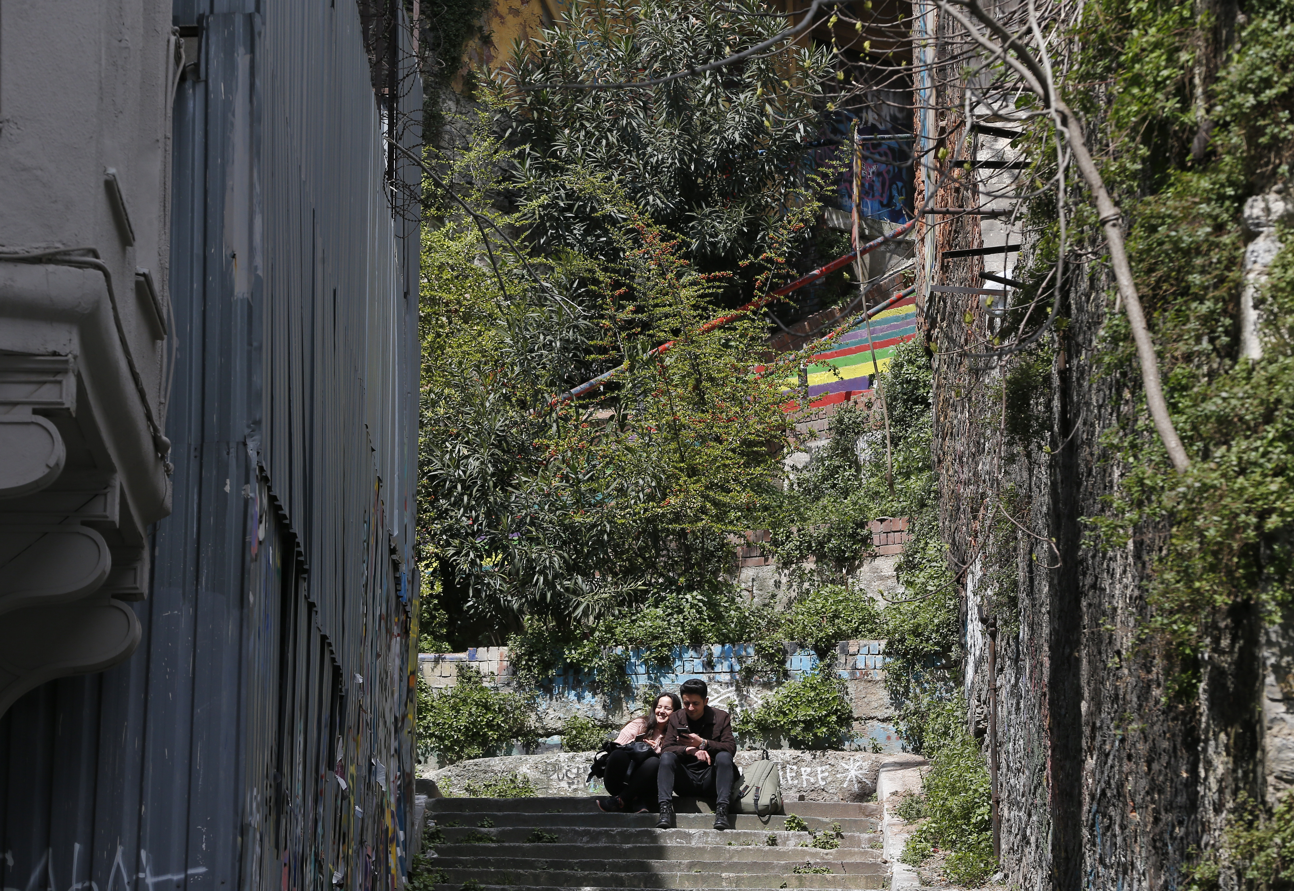 In this Thursday, April 4, 2019 photo, a couple sits in Istanbul's fashionable Cihangir neighbourhood. The mood among opposition supporters in Turkey's biggest city is one of jubilation but also worry - fear that their win in Istanbul's mayoral race could be overturned in a recount taking place after the ruling party challenged the election results. (AP Photo/Lefteris Pitarakis)
