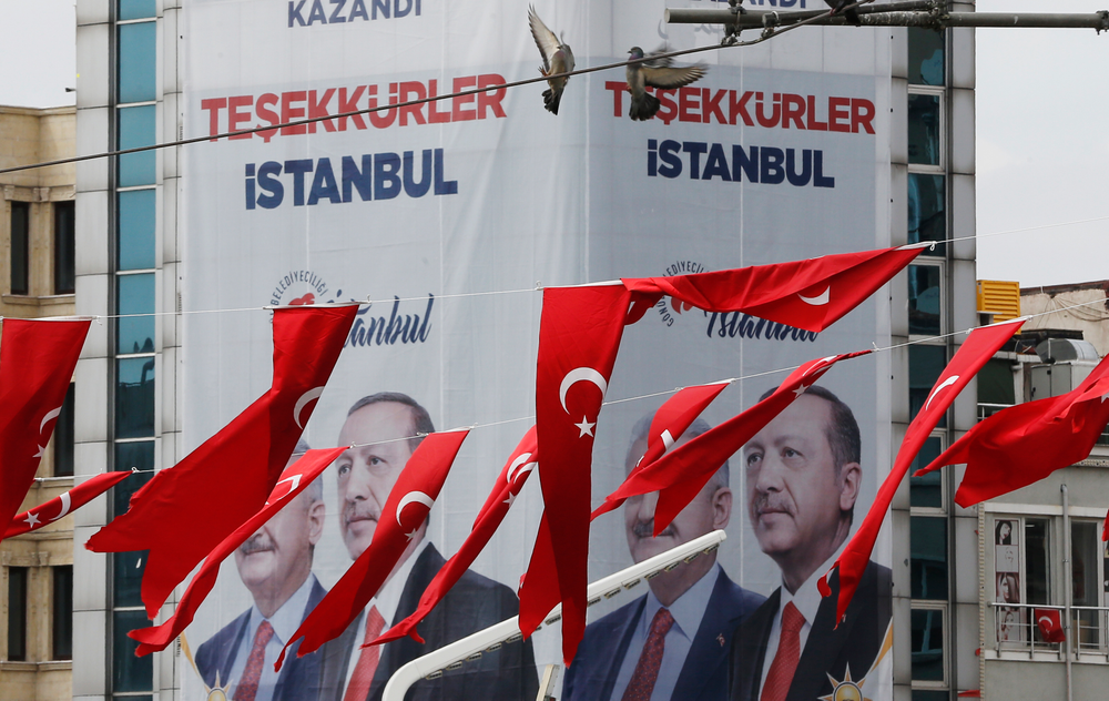 In this Thursday, April 4, 2019 photo, Turkish flags fly in Istanbul Taksim's square while in the background posters showing Binali Yildirim, left, the mayoral candidate for Istanbul of Turkey's President Recep Tayyip Erdogan's ruling Justice and Development Party's (AKP) and Erdogan are seen. The posters reads in Turkish: 'Thank you, Istanbul'. The mood among opposition supporters in Turkey's biggest city is one of jubilation but also worry - fear that their win in Istanbul's mayoral race could be overturned in a recount taking place after the ruling party challenged the election results. (AP Photo/Lefteris Pitarakis)