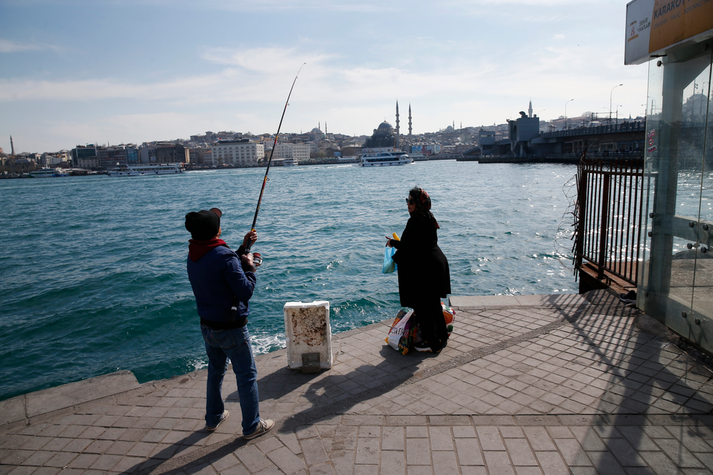 In this Thursday, April 4, 2019 photo, a man fishes at the Golden Horn as a woman waits for the boat to cross the Bosporus Strait from Europe to Asia, in Istanbul. The mood among opposition supporters in Turkey's biggest city is one of jubilation but also worry - fear that their win in Istanbul's mayoral race could be overturned in a recount taking place after the ruling party challenged the election results. (AP Photo/Lefteris Pitarakis)