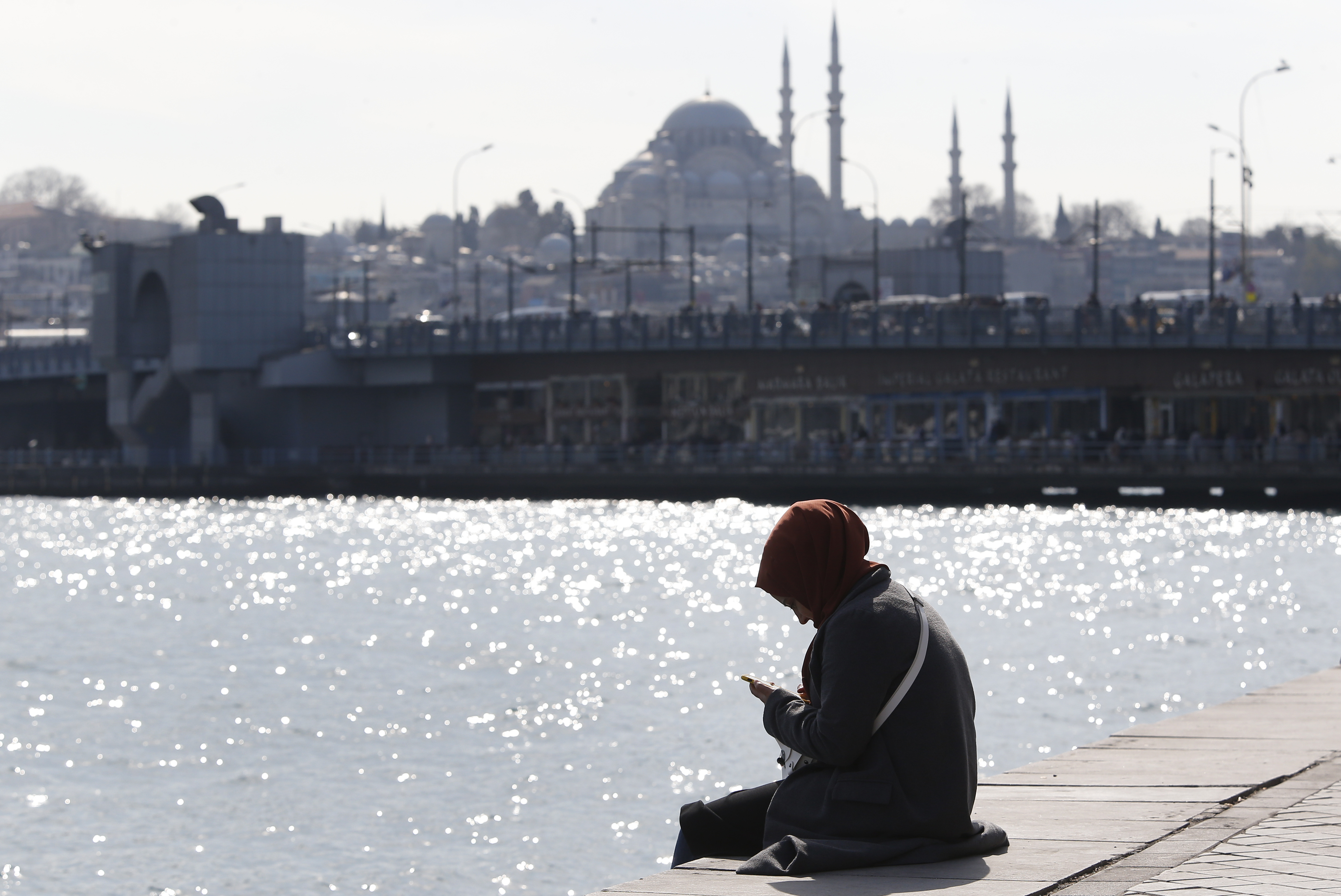 In this Thursday, April 4, 2019 photo, a woman, backdropped by the Suleymaniye mosque, sits by the Golden Horn in Istanbul. The mood among opposition supporters in Turkey's biggest city is one of jubilation but also worry - fear that their win in Istanbul's mayoral race could be overturned in a recount taking place after the ruling party challenged the election results. (AP Photo/Lefteris Pitarakis)