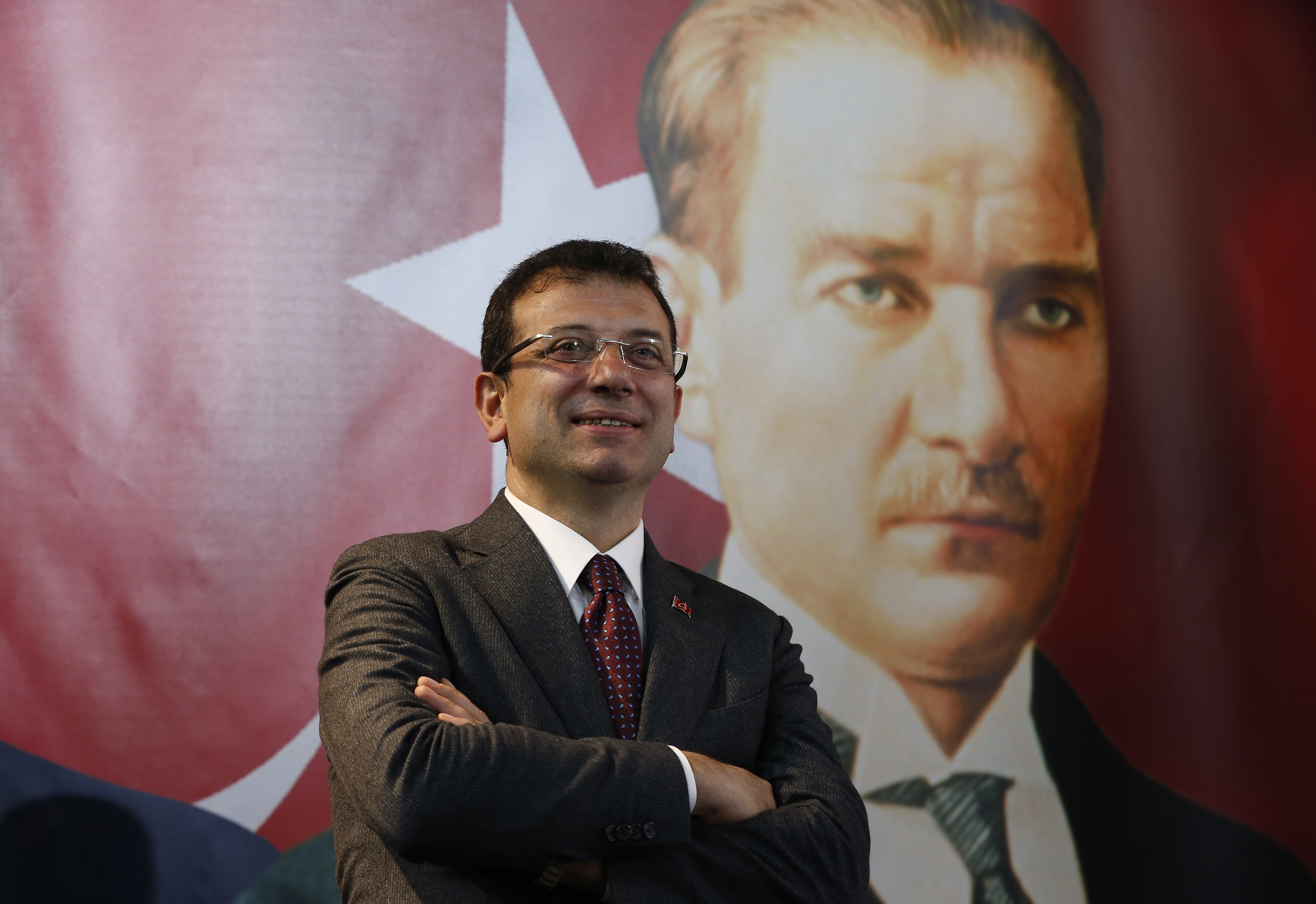 In this Thursday, April 4, 2019 photo, backdropped by a poster of modern Turkey's founder Mustafa Kemal Ataturk, right, Ekrem Imamoglu, the opposition, Republican People's Party's (CHP) mayoral candidate in Istanbul, poses for The Associated Press following an interview in Istanbul. The mood among opposition supporters in Turkey's biggest city is one of jubilation but also worry - fear that their win in Istanbul's mayoral race could be overturned in a recount taking place after the ruling party challenged the election results. (AP Photo/Lefteris Pitarakis)