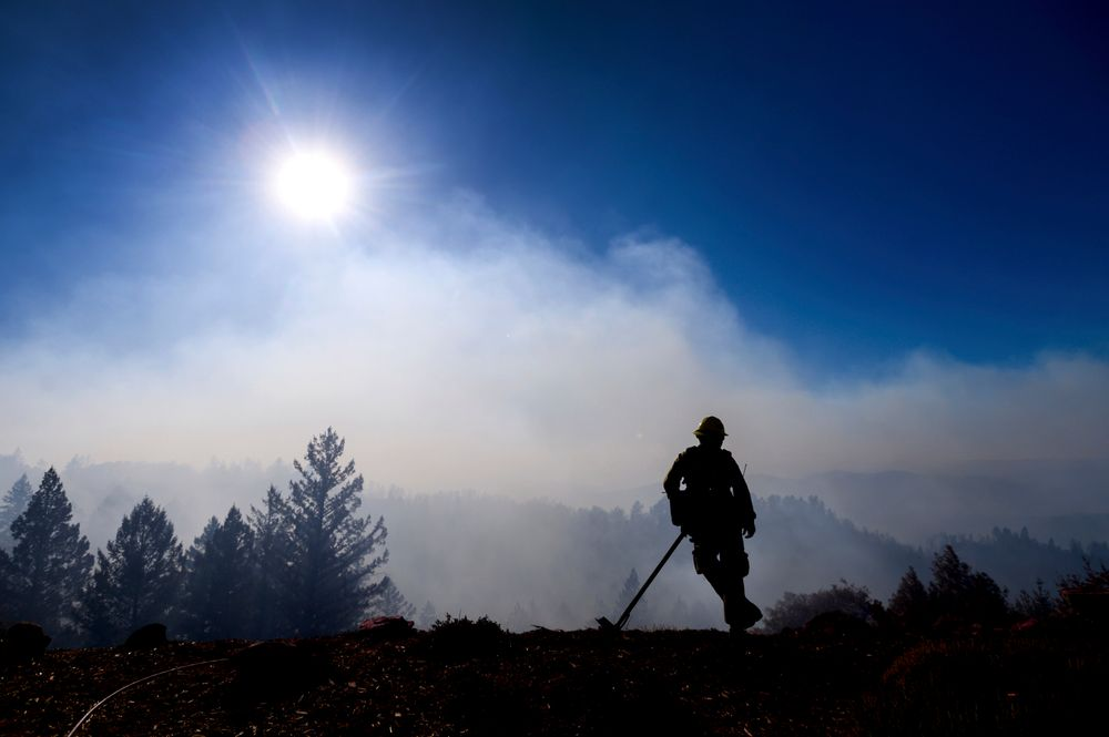 Firefighter Josh Petrell monitors the Kincade Fire burning near Healdsburg, Calif., on Tuesday, Oct. 29, 2019. The overall weather picture in northern areas is improving as powerful, dry winds bring extreme fire weather to Southern California. (AP Photo/Noah Berger)