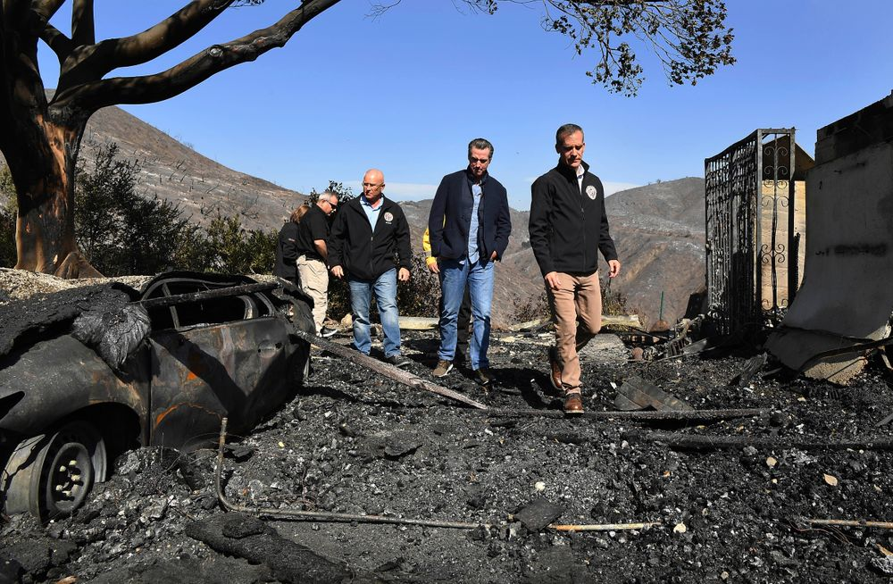 From left, L.A. City Councilman Mike Bonin, California Governor Gavin Newsom and L.A. City Mayor Eric Garcetti tour a burned home along Tigertail Road in Brentwood, Calif., Tuesday Oct. 29, 2019. (Wally Skalij/Los Angeles Times via AP, Pool)