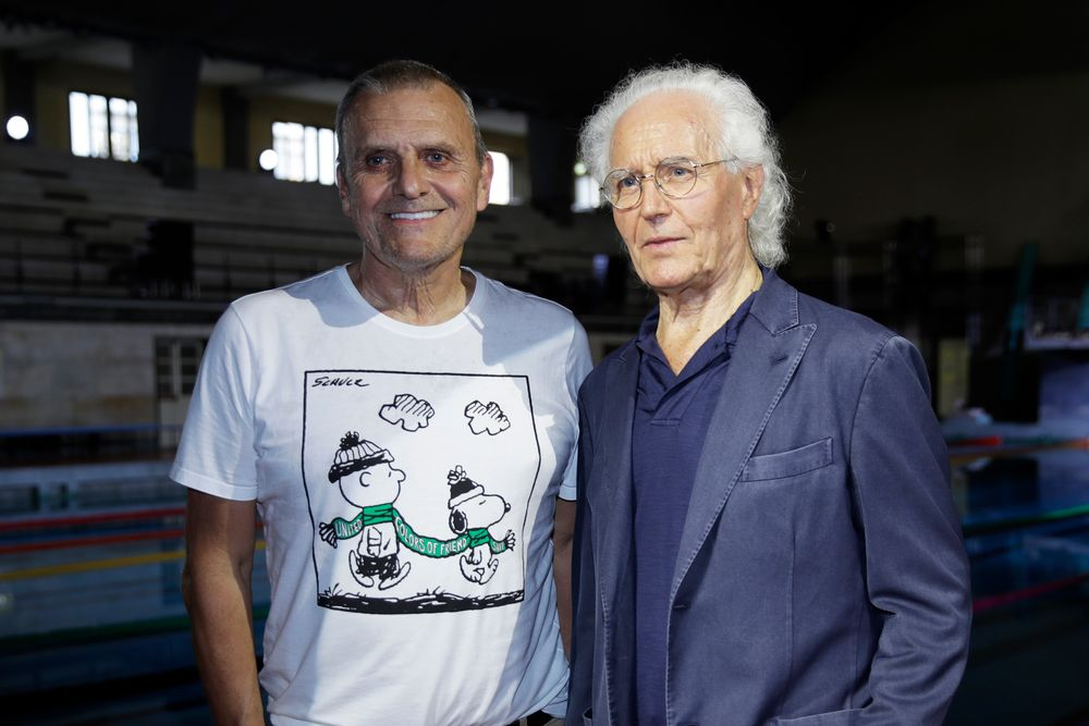 Designer Jean-Charles de Castelbajac, left, and Luciano Benetton, co founder of the Benetton group, pose for photographers at the conclusion of the Benetton Spring-Summer 2020 collection, unveiled during the fashion week, in Milan, Italy, Tuesday, Sept. 17, 2019. (AP Photo/Luca Bruno)