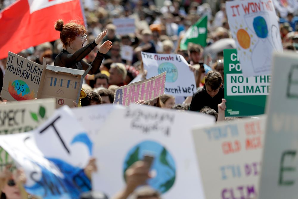A woman is lifted above the crowd as thousands of protestors, many of them school students, gather in Sydney, Friday, Sept. 20, 2019, calling for action to guard against climate change. Australia's acting Prime Minister Michael McCormack has described ongoing climate rallies as