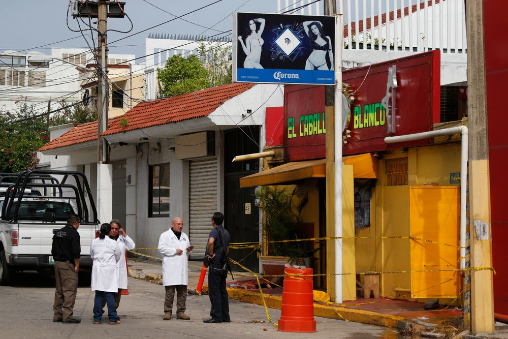Investigators work outside the White Horse nightclub, the scene of a Tuesday night attack that killed more than two dozen staff and patrons, in Coatzacoalcos, Veracruz state, Mexico, Thursday, Aug. 29, 2019. Anger is mounting among relatives of 28 people who died horrendously when gang members set the nightclub on fire after blocking its exits. The families complained that criminals are out of control and making life impossible in this southern Mexico oil town. (AP Photo/Rebecca Blackwell)