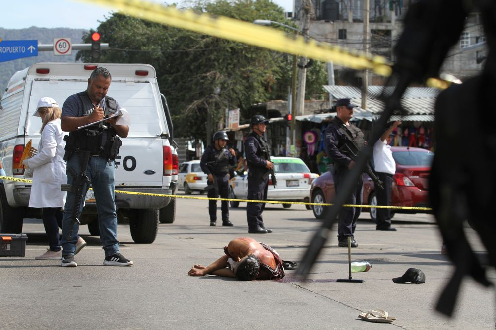 FILE - In this June 2, 2019 file photo, the body of a bloodied man lies in the middle of a street where police and forensic workers secure the crime scene in Acapulco, Mexico. Mexico's drug war appears to be back, and it may be worse this time around than in the bloody years of the government's 2006-2012 offensive against drug cartels. Back then, the worst of the violence was confined to a few cities. Now it is spread throughout the country. (AP Photo/Bernardindo Hernandez, File)