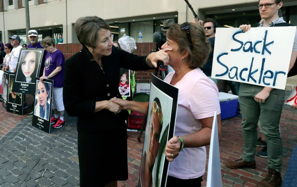Massachusetts Attorney General Maura Healey, left, wipes a tear from the face of Wendy Werbiskis, of East Hampton, Mass., one of the protesters gathered on Friday, Aug. 2, 2019, outside a courthouse in Boston, where a judge was to hear arguments in state's lawsuit against Purdue Pharma over its role in the national drug epidemic. Organizers said they wanted to continue to put pressure on the Connecticut pharmaceutical company and the Sackler family that owns it. Werbiskis lost her son to an overdose two years ago. (AP Photo/Charles Krupa)