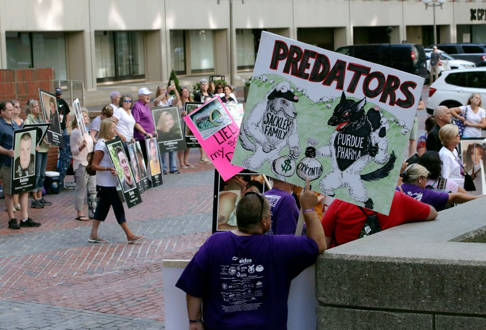 Protesters gather outside a courthouse on Friday, Aug. 2, 2019, in Boston, where a judge was to hear arguments in Massachusetts' lawsuit against Purdue Pharma over its role in the national drug epidemic. Organizers said they wanted to continue to put pressure on the Connecticut pharmaceutical company and the Sackler family that owns it.  (AP Photo/Charles Krupa)