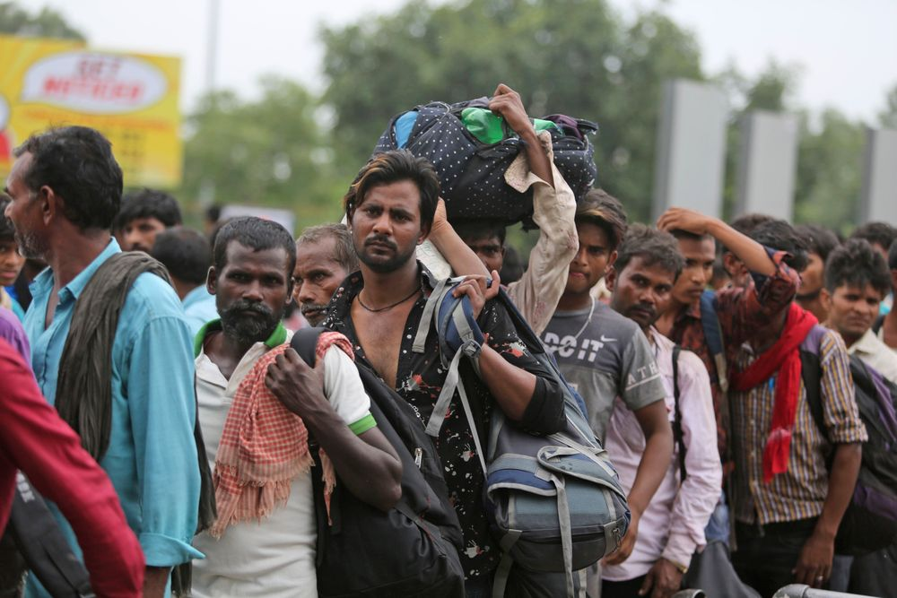 Indian migrant laborers carry their luggage and prepare to leave the region, at a railway station in Jammu, India, Wednesday, Aug. 7, 2019. Indian lawmakers passed a bill Tuesday that strips statehood from the Indian-administered portion of Muslim-majority Kashmir, which remains under an indefinite security lockdown, actions that archrival Pakistan warned could lead to war. (AP Photo/Channi Anand)