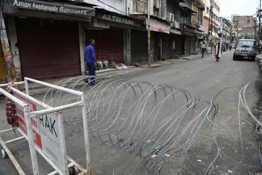 A pedestrian walks past a barbwire barricade set up by security officers in Jammu, India, Wednesday, Aug. 7, 2019. Indian lawmakers passed a bill Tuesday that strips statehood from the Indian-administered portion of Muslim-majority Kashmir, which remains under an indefinite security lockdown, actions that archrival Pakistan warned could lead to war. (AP Photo/Channi Anand)