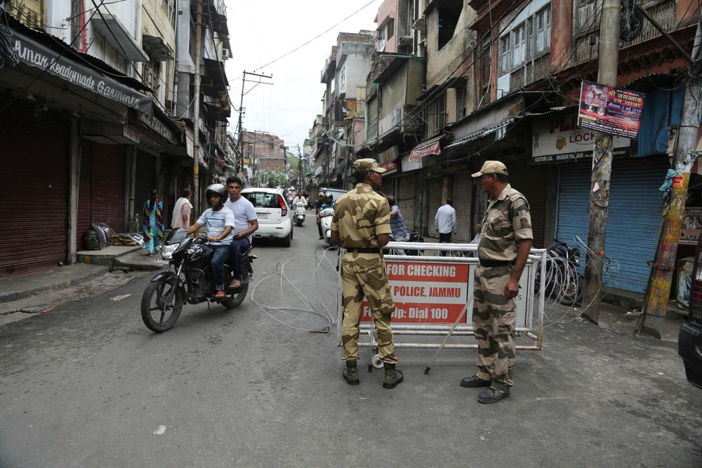 Security officers stand guard near a barricade in Jammu, India, Wednesday, Aug. 7, 2019. Indian lawmakers passed a bill Tuesday that strips statehood from the Indian-administered portion of Muslim-majority Kashmir, which remains under an indefinite security lockdown, actions that archrival Pakistan warned could lead to war. (AP Photo/Channi Anand)