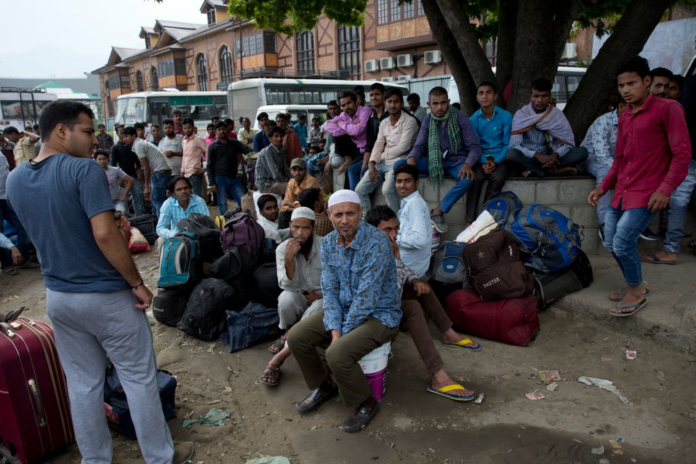 In this Tuesday, Aug. 6, 2019 photo, Indian migrant workers wait outside the government transport yard waiting to buy bus tickets to leave the region, during curfew in Srinagar, Indian controlled Kashmir. Hit by a complete security lockdown in Kashmir, hundreds of poor migrant workers have begun fleeing the Himalayan region to return to their far-away villages in northern and eastern India. (AP Photo/ Dar Yasin)
