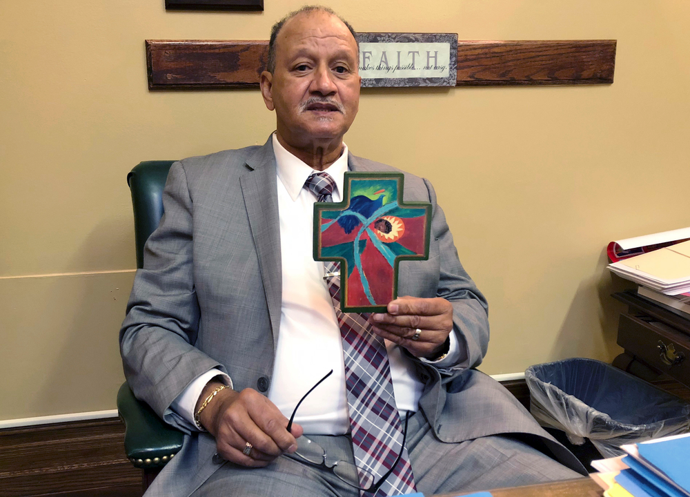 In this Wednesday, May 22, 2019, photo state Democratic Sen. Harold Metts, of Providence, holds one of the crosses decorating his office at the Statehouse in Providence, R.I. Metts, a Baptist deacon, voted against a bill to preserve federal abortion protections in Rhode Island state law, which failed in committee. (AP Photo/Jennifer McDermott)