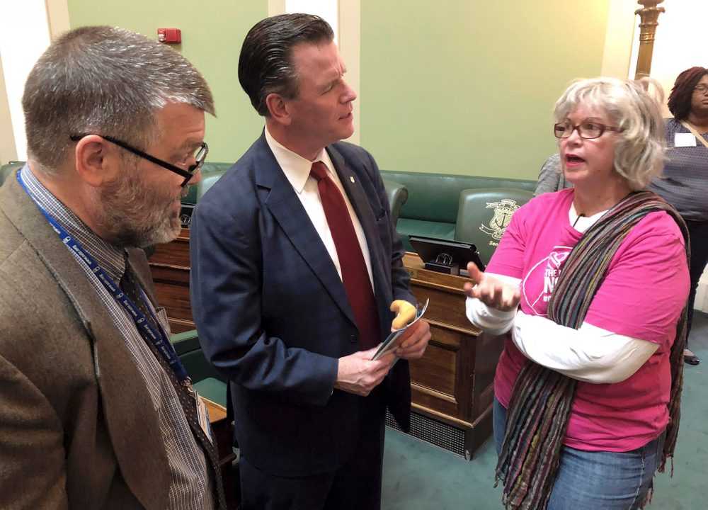 In this Wednesday, May 22, 2019, photo, Democratic State Sen. Stephen Archambault, of Smithfield, center, explains why he voted against a bill to preserve federal abortion protections in Rhode Island state law to Barth Bracy, left, of Rhode Island Right to Life, and San Shoppell, right, of Riverside, a Planned Parenthood volunteer, at the Statehouse in Providence, R.I. Archambault was the swing vote in the Senate Judiciary Committee, which defeated the bill. (AP Photo/Jennifer McDermott