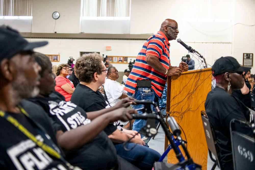 Flint resident Arthur Woodson expresses his anger and disappointment at the podium as the first resident to speak during a community meeting with Flint water prosecutors at UAW Local 659, Friday, June 28, 2019, in Flint, Mich. Michigan Solicitor General Fadwa Hammoud and Wayne County Prosecutor Kym Worthy spoke to about 100 residents at a union hall in the city, two weeks after dismissing charges against the former state health director and other officials. The three-year probe was relaunched, and charges could be refiled. (Jake May/MLive.com/The Flint Journal via AP)