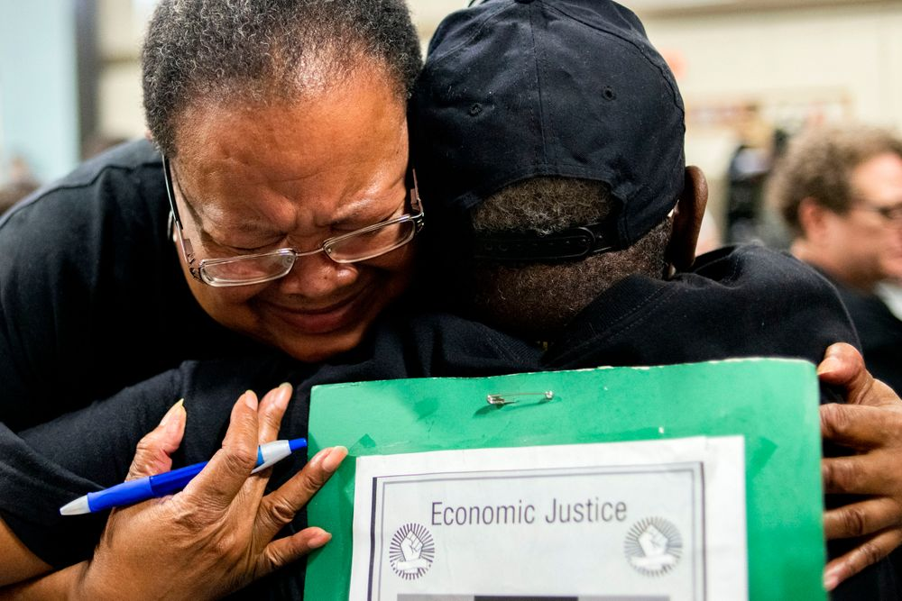 Marijoyce Campbell, a 65-year-old lifelong Flint resident, cries in the arms of a friend after speaking her mind at the podium during a community meeting with Flint water prosecutors at UAW Local 659, Friday, June 28, 2019, in Flint, Mich. Michigan Solicitor General Fadwa Hammoud and Wayne County Prosecutor Kym Worthy spoke to about 100 residents Friday night at a union hall in the city, two weeks after dismissing charges against the former state health director and other officials. (Jake May/MLive.com/The Flint Journal via AP)