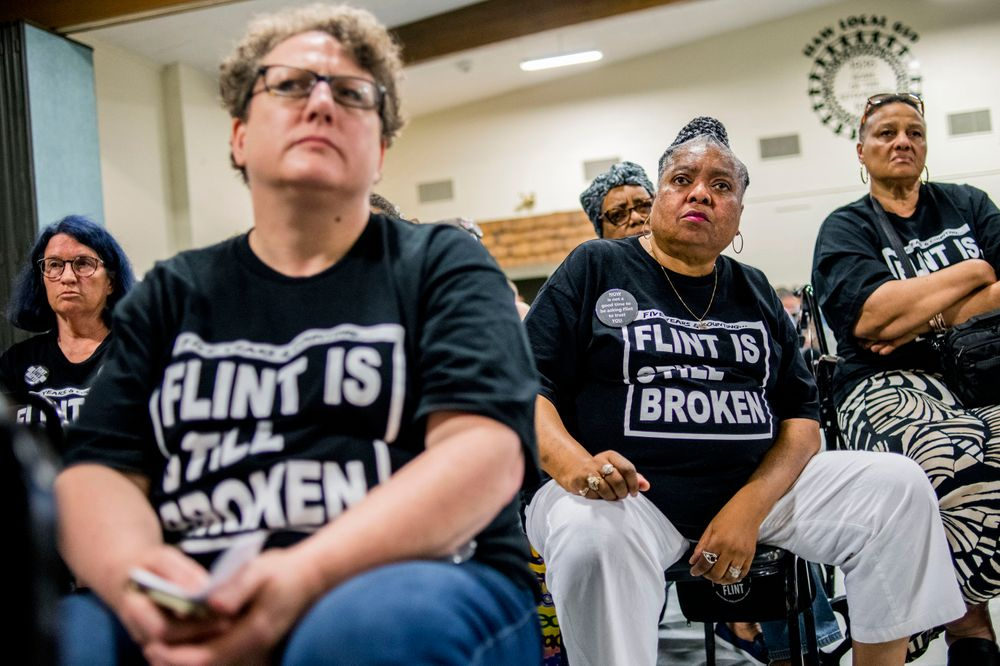 Claudia Perkins-Milton, second right, joins other Flint residents as they show their determination while asking heartfelt, serious questions to Michigan Solicitor General Fadwa Hammoud and Wayne County Prosecutor Kym Worthy during a community meeting with Flint water prosecutors at UAW Local 659 on Friday, June 28, 2019, in Flint, Mich. Prosecutors who dropped charges against eight people in the Flint water scandal explained their decision in a public forum Friday night, telling frustrated and shocked residents they must look at hundreds of mobile devices and millions of documents that a previous investigative team never reviewed. (Jake May/MLive.com/The Flint Journal via AP)