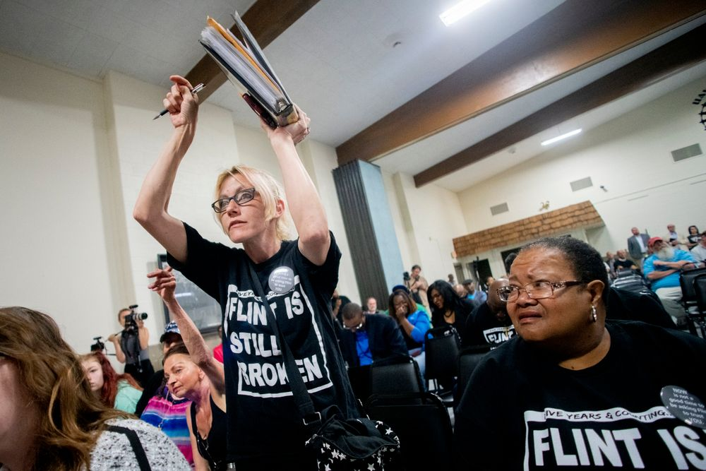 Flint resident Christina Murphy stands up and points at a binder of documents she has kept while listening to answers to resident questions from Michigan Solicitor General Fadwa Hammoud and Wayne County Prosecutor Kym Worthy as about 100 area residents gathered during a community meeting with Flint water prosecutors at UAW Local 659, Friday, June 28, 2019, in Flint, Mich. Michigan Solicitor General Fadwa Hammoud and Wayne County Prosecutor Kym Worthy spoke to residents Friday night, two weeks after dismissing charges against the former state health director and other officials. (Jake May/MLive.com/The Flint Journal via AP)