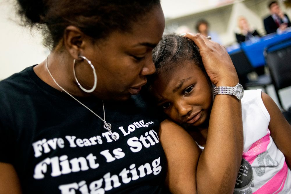 Flint resident Ariana Hawk consoles her daughter Aliana, 4, nearing the end of a two-hour community meeting with Flint water prosecutors at UAW Local 659, Friday, June 28, 2019, in Flint, Mich. Hawk is the mother of Sincere Smith, who graced the cover of Time magazine at the height of the Flint water crisis in 2016. Michigan Solicitor General Fadwa Hammoud and Wayne County Prosecutor Kym Worthy spoke to about 100 residents Friday night at a union hall in the city, two weeks after dismissing charges against the former state health director and other officials. (Jake May/MLive.com/The Flint Journal via AP)