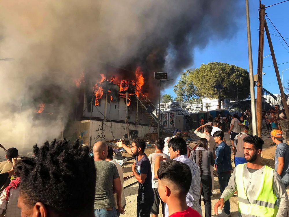 Migrants and refugees stand next to burning house containers at the Moria refugee camp, on the northeastern Aegean island of Lesbos, Greece, Sunday, Sept. 29, 2019. Migrants protesting at an overcrowded camp on the Greek island of Lesbos set fires and clashed with police Sunday, authorities said. Police and local authorities said there were unconfirmed reports of two fatalities at the Moria camp. (InTime News via AP)
