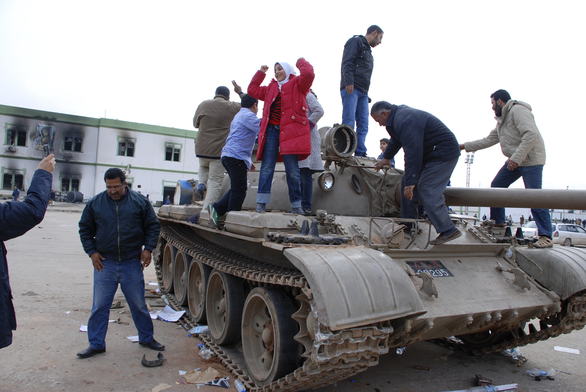 FILE - In this Feb. 21, 2011 file photo, people stand on a tank inside a security forces compound in the eastern Libyan city of Benghazi. Libyans are celebrating the eighth anniversary of their 2011 uprising that led to the overthrow and killing of longtime dictator Moammar Gadhafi, although the intensity of the festivities is underlining the split between the country's east and west. Hundreds of people reveled Sunday in the western cities of Tripoli, Misrata and Zawiya, where bands played and flags lined the streets. (AP Photo/Alagur, File)