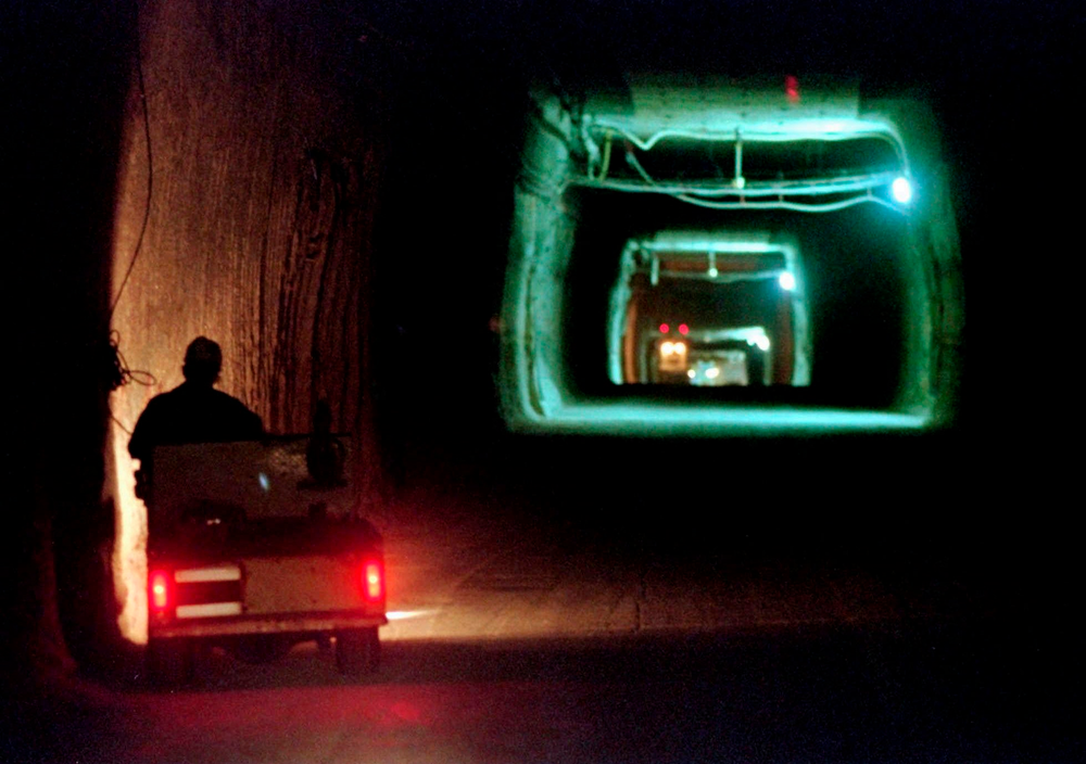 FILE - In this April 8, 1998, file photo, a worker drives a cart through a tunnel inside the Waste Isolation Pilot Plant No. 2, 150 feet below the surface near Carlsbad, N.M.   Twenty years and more than 12,330 shipments later, tons of Cold War-era radioactive waste from decades of bomb-making and research have been stashed in the salt caverns that make up the underground facility and not without issues.  (AP Photo/Eric Draper, File)