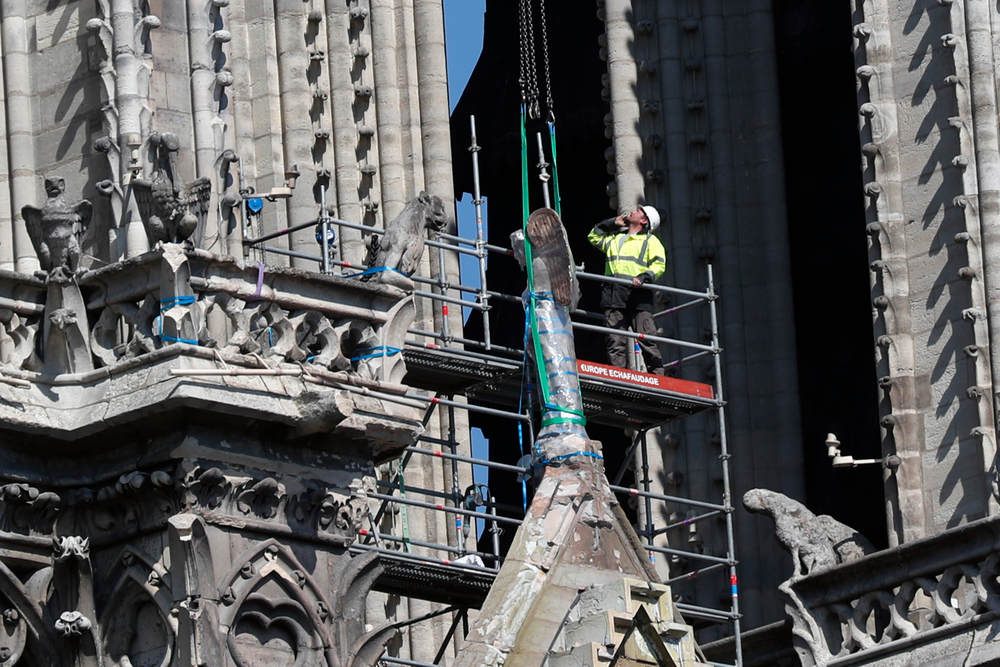 A worker prepares to remove a statue from the damaged Notre Dame cathedral, in Paris, Friday, April 19, 2019. Rebuilding Notre Dame, the 800-year-old Paris cathedral devastated by fire this week, will cost billions of dollars as architects, historians and artisans work to preserve the medieval landmark. (AP Photo/Thibault Camus)