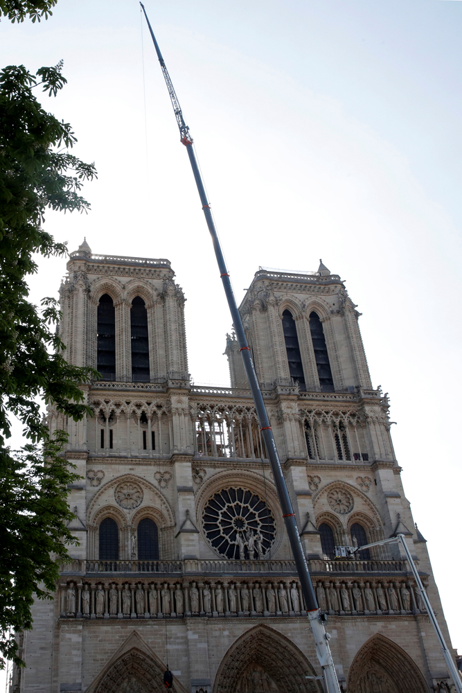 A crane works at Notre-Dame cathedral in Paris, Friday, April 19, 2019. Rebuilding Notre Dame, the 800-year-old Paris cathedral devastated by fire this week, will cost billions of dollars as architects, historians and artisans work to preserve the medieval landmark. (Philippe Wojazer/Pool via AP)