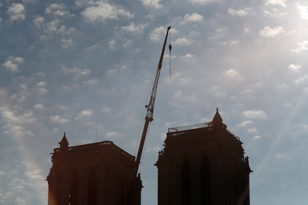 A crane is seen between the belfries of Notre Dame cathedral, in Paris, Friday, April 19, 2019. Rebuilding Notre Dame, the 800-year-old Paris cathedral devastated by fire this week, will cost billions of dollars as architects, historians and artisans work to preserve the medieval landmark. (AP Photo/Thibault Camus)