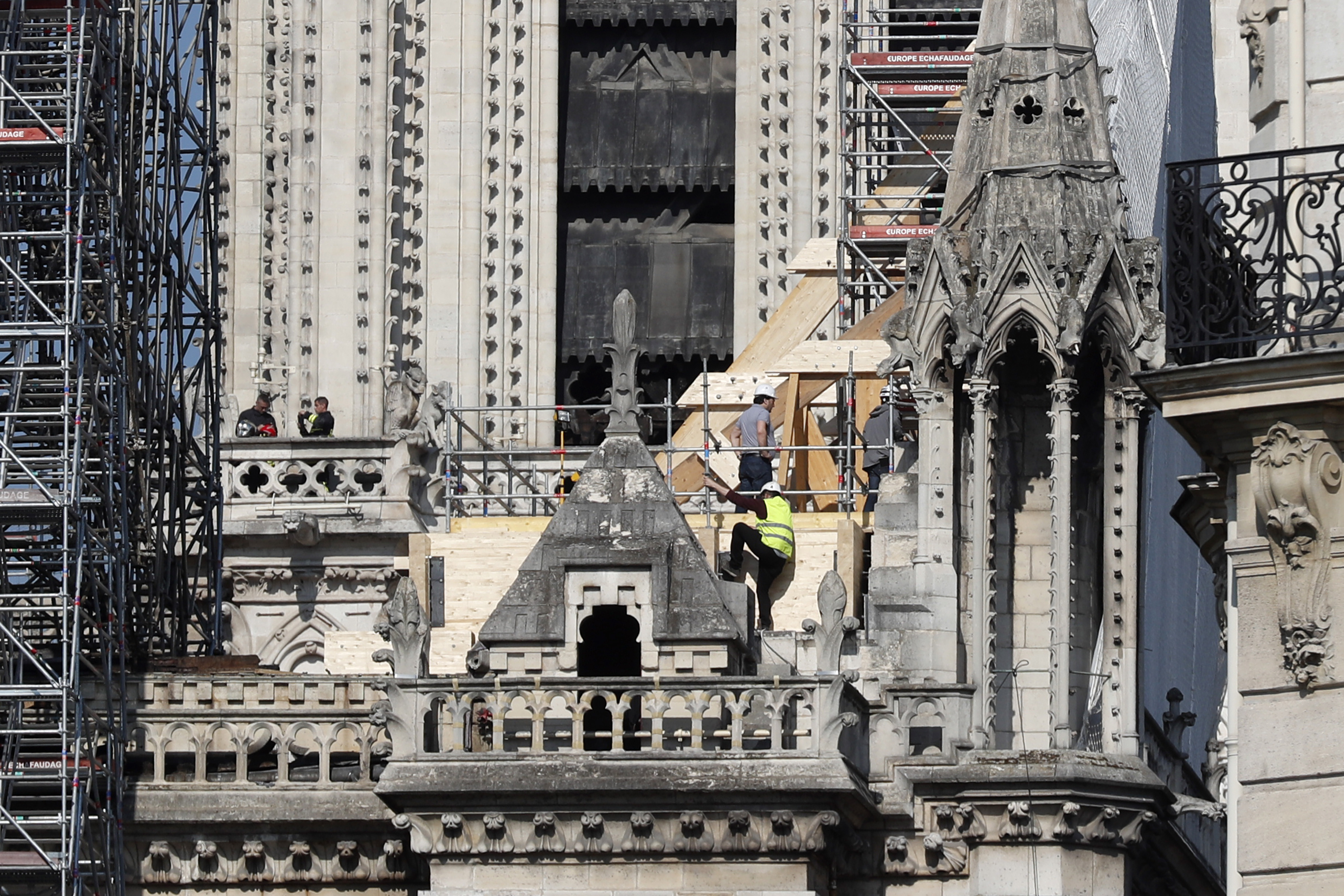 Workers stand by wooden planks supporting Notre Dame cathedral Friday, April 19, 2019 in Paris. Rebuilding Notre Dame, the 800-year-old Paris cathedral devastated by fire this week, will cost billions of dollars as architects, historians and artisans work to preserve the medieval landmark. (AP Photo/Thibault Camus)