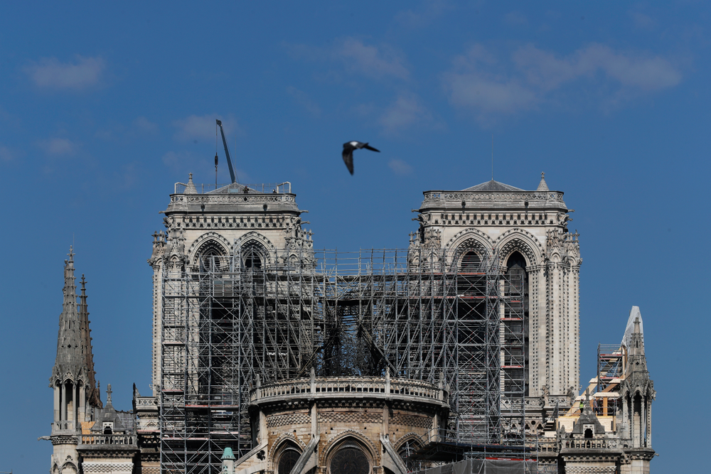 A pigeon flies over Notre Dame cathedral, in Paris, Friday, April 19, 2019. Rebuilding Notre Dame, the 800-year-old Paris cathedral devastated by fire this week, will cost billions of dollars as architects, historians and artisans work to preserve the medieval landmark. (AP Photo/Thibault Camus)