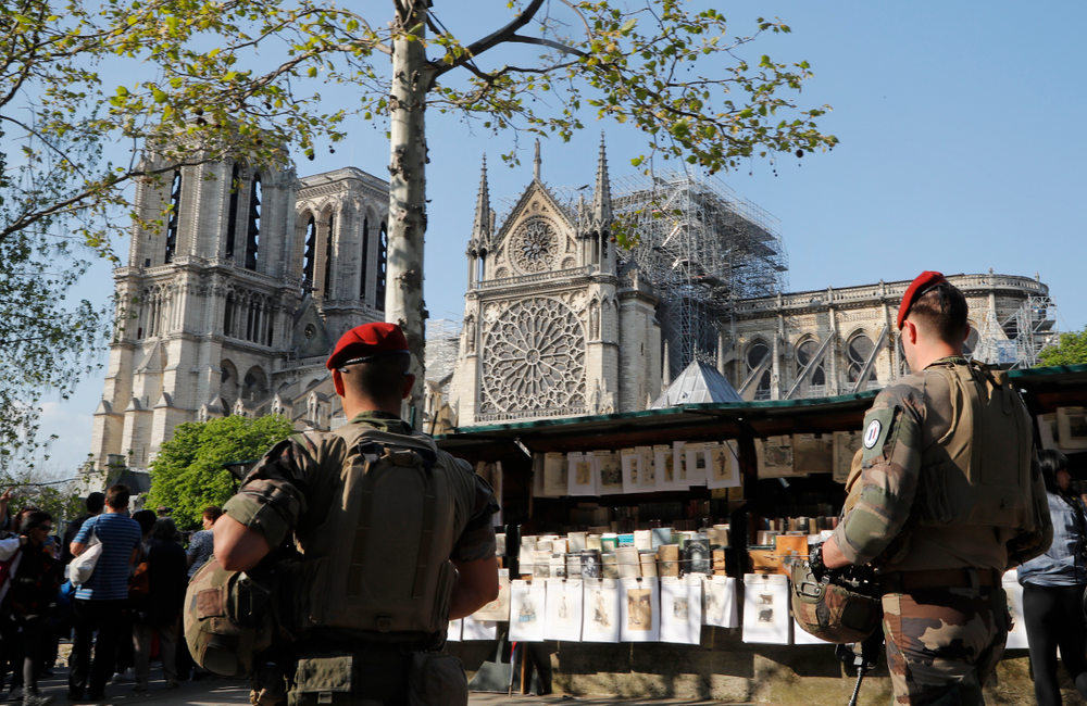 French soldiers patrol along the Notre Dame Cathedral in Paris, Friday, April 19, 2019. Rebuilding Notre Dame, the 800-year-old Paris cathedral devastated by fire this week, will cost billions of dollars as architects, historians and artisans work to preserve the medieval landmark. (AP Photo/Michel Euler)