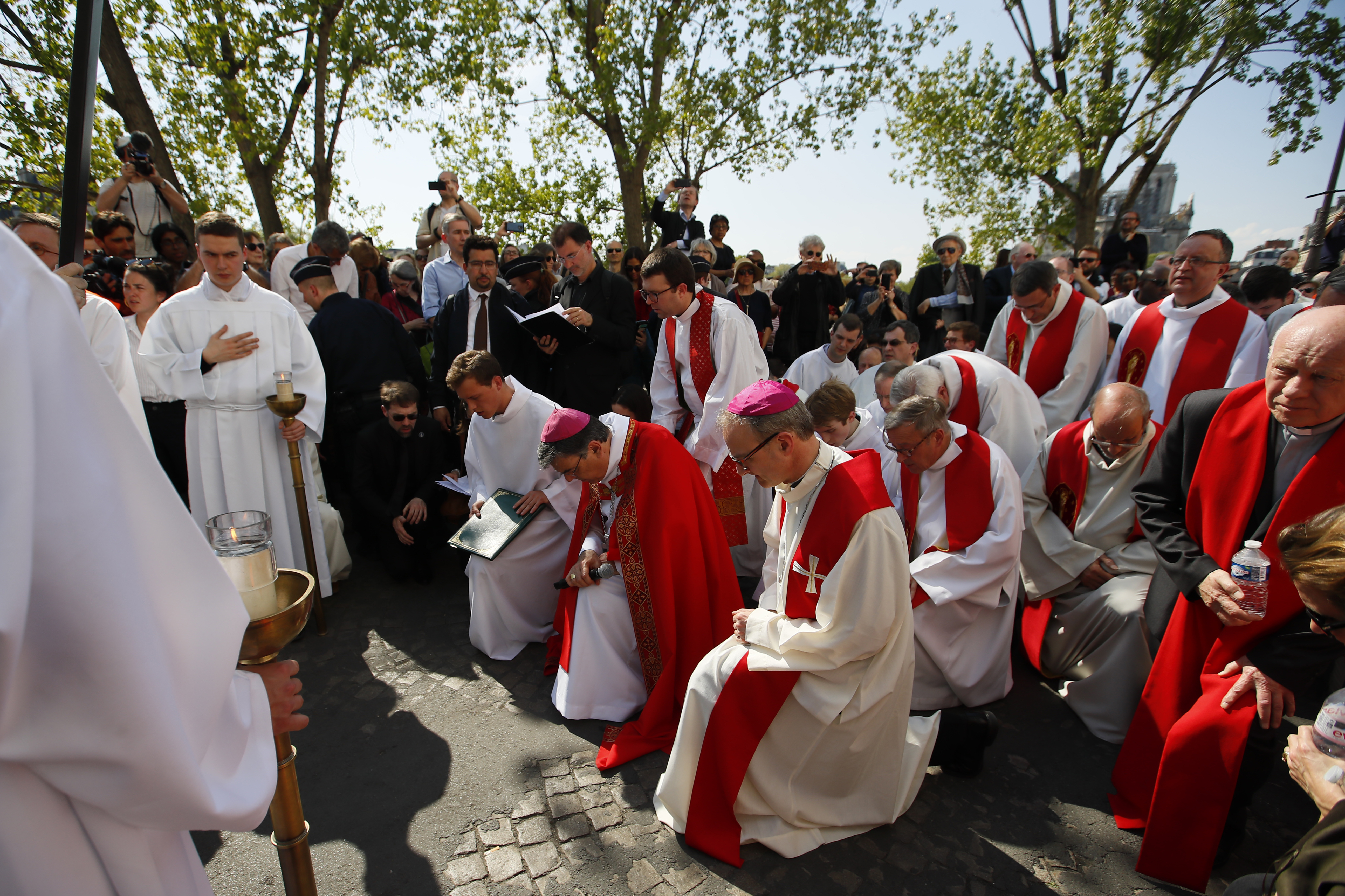 With Notre Dame cathedral, background right, religious officials pray during the Good Friday procession, Friday, April 19, 2019 in Paris. Top French art conservation officials say the works inside Notre Dame suffered no major damage in the fire that devastated the cathedral, and the pieces have been removed from the building for their protection.(AP Photo/Francois Mori)