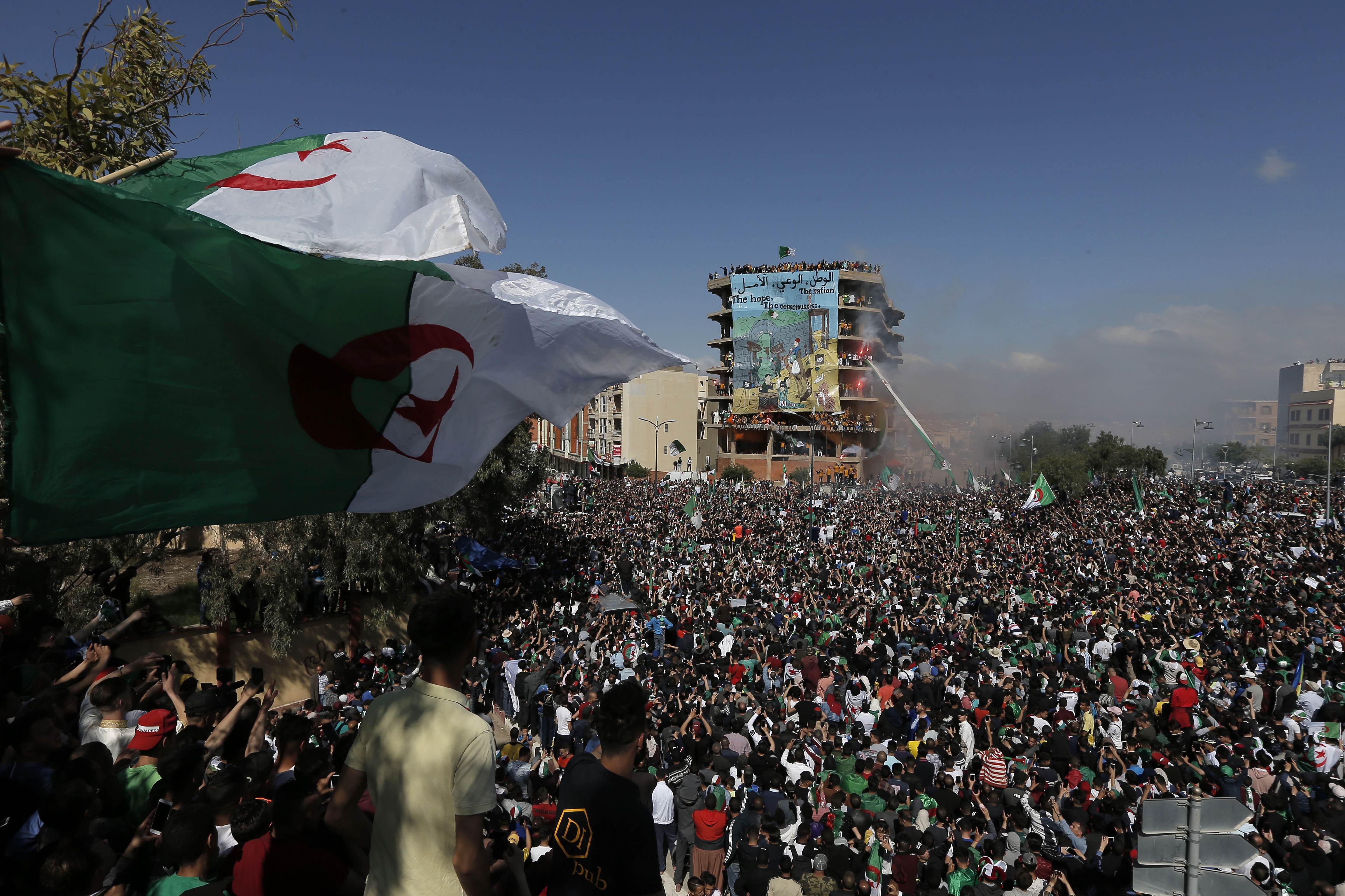 Demonstrators carry a giant Algerian flag during a protest in Bordj Bou Arreridj, east of Algiers, Friday, April 26, 2019. Algerians are massing for a 10th week of protests against their country's ruling class, calling for the ex-president's brother to be put on trial. (AP Photo/Toufik Doudou)