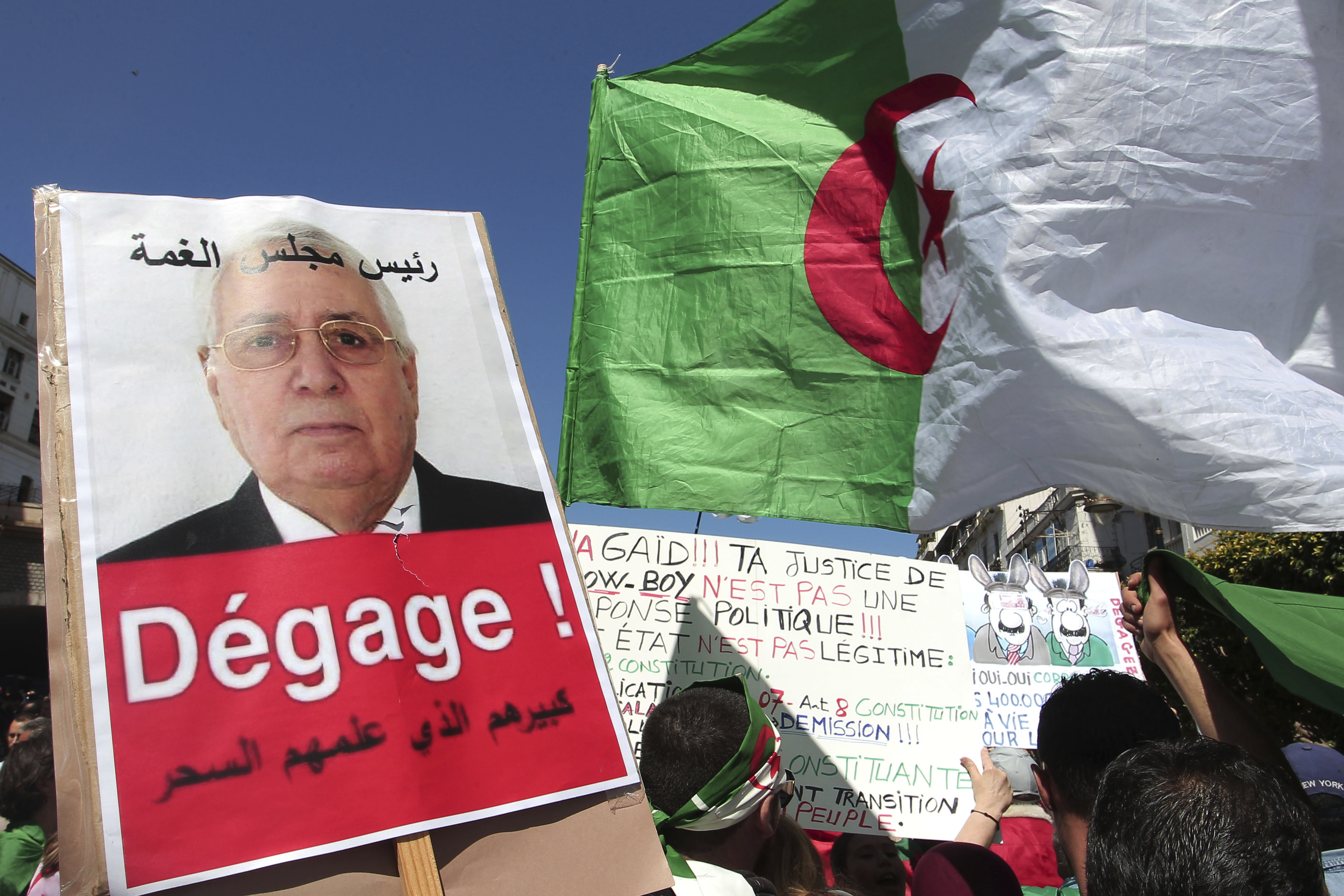A demonstrator holds a placard showing Abdelkader Bensalah and reading