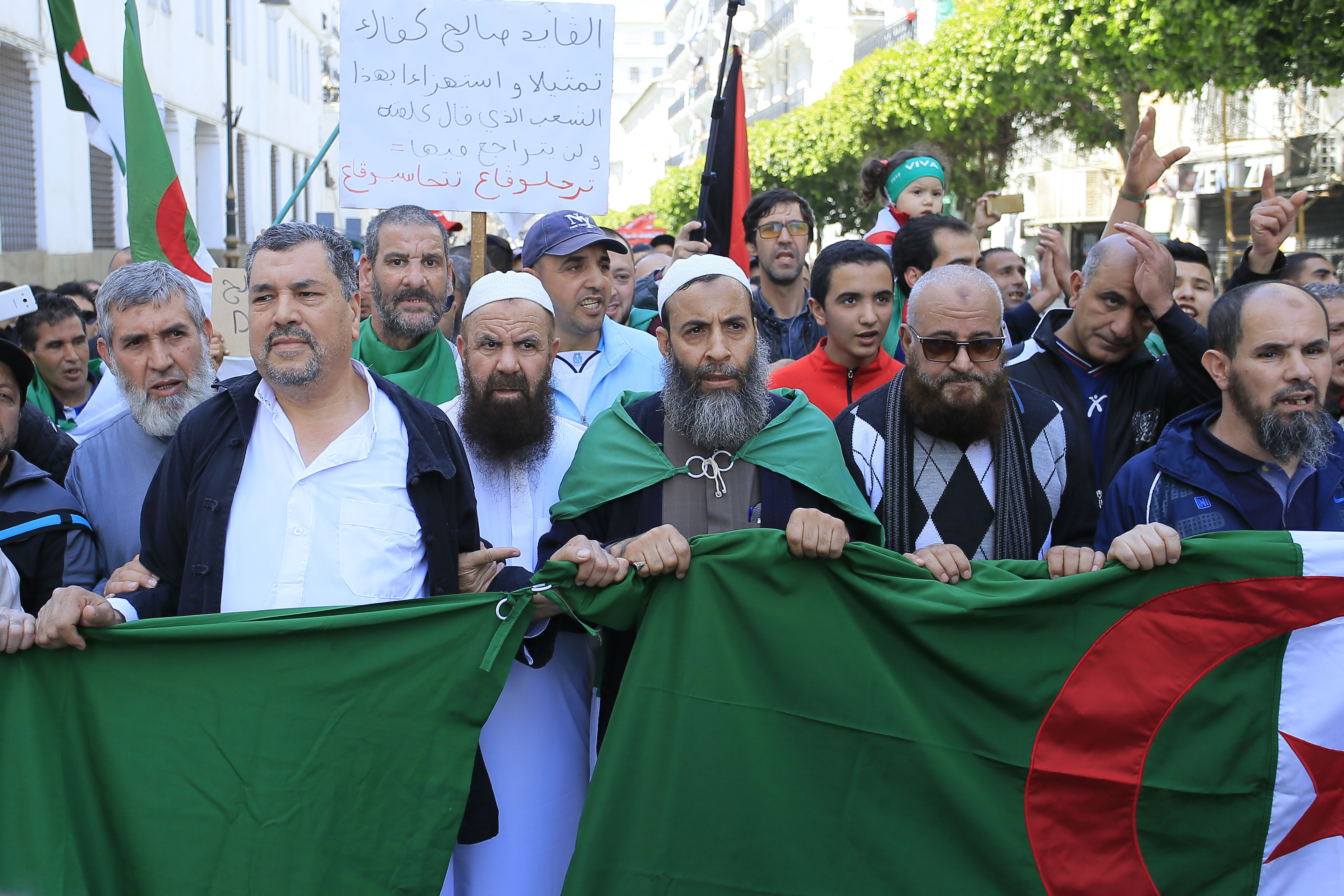 Demonstrators march with the Algerian flag during a protest in Algiers, Friday, April 26, 2019. Algerians are massing for a 10th week of protests against their country's ruling class, calling for the ex-president's brother to be put on trial. (AP Photo/Anis Belghoul)