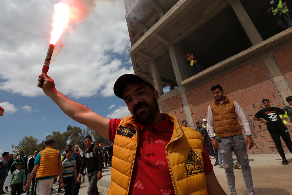A demonstrator lights a flare during a protest in Bordj Bou Arreridj, east of Algiers, Friday, April 26, 2019. Algerians are massing for a 10th week of protests against their country's ruling class, calling for the ex-president's brother to be put on trial. (AP Photo/Toufik Doudou)