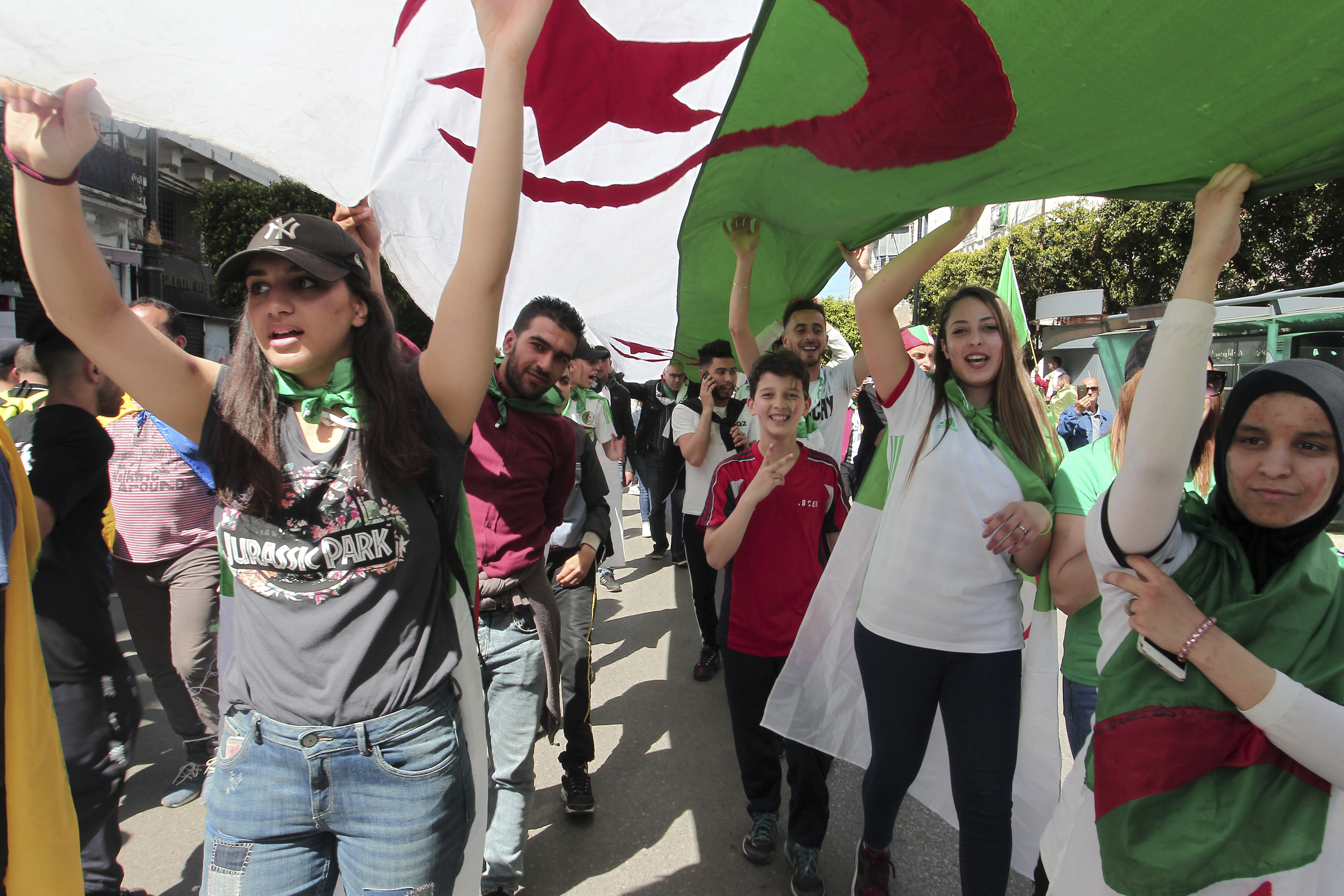 Demonstrators carry a giant Algerian flag during a protest in Algiers, Friday, April 26, 2019. Algerians are massing for a 10th week of protests against their country's ruling class, calling for the ex-president's brother to be put on trial. (AP Photo/Fateh Guidoum)