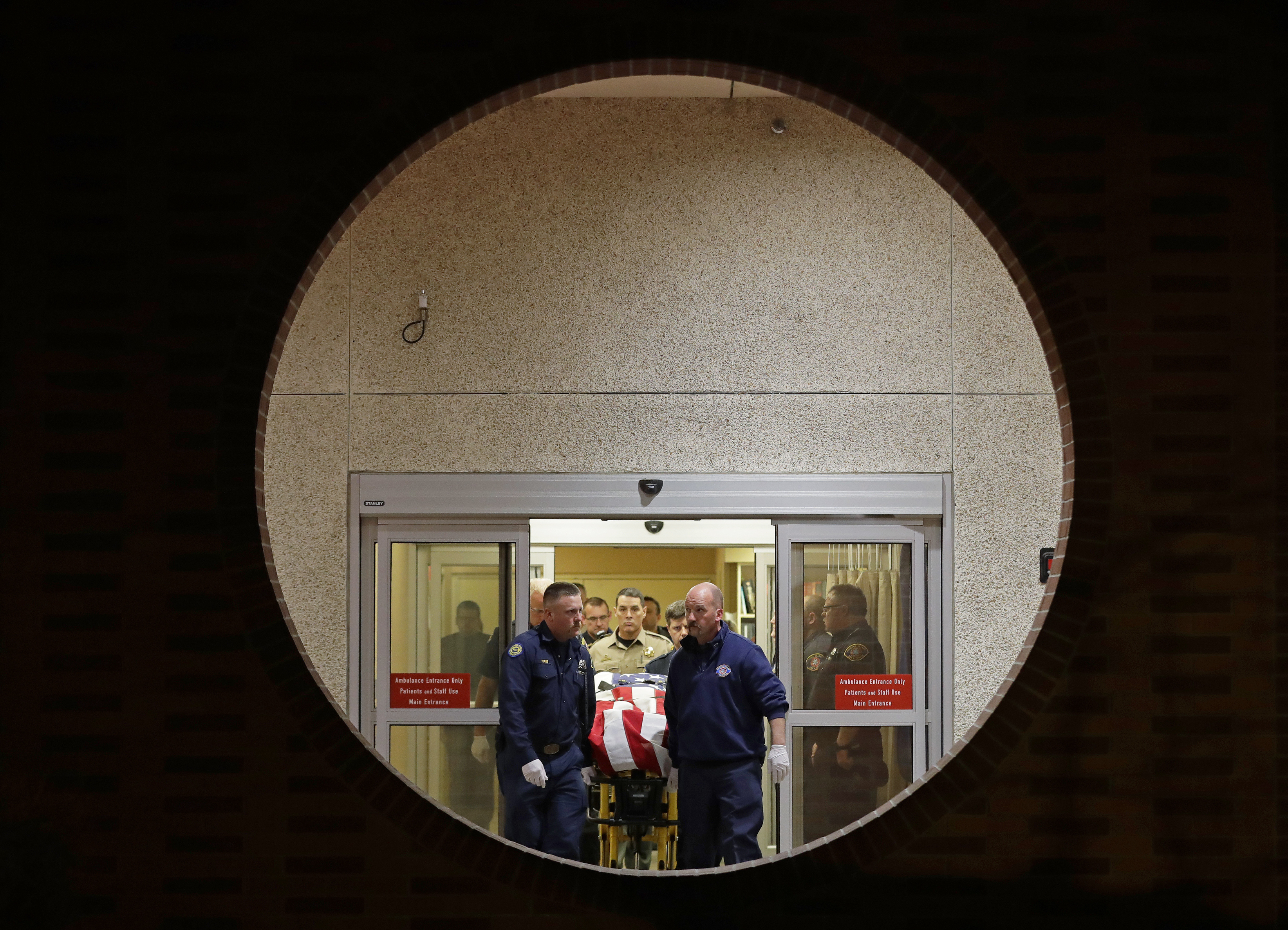 The body of a Kittitas County Sheriff's deputy is draped with a U.S. flag as it is carried out of Kittitas Valley Healthcare Hospital in the early morning hours of Wednesday, March 20, 2019, in Ellensburg, Wash., as seen through a large circular entry window. A sheriff's deputy was killed and a police officer was injured after an exchange of gunfire during an attempted traffic stop. (AP Photo/Ted S. Warren)