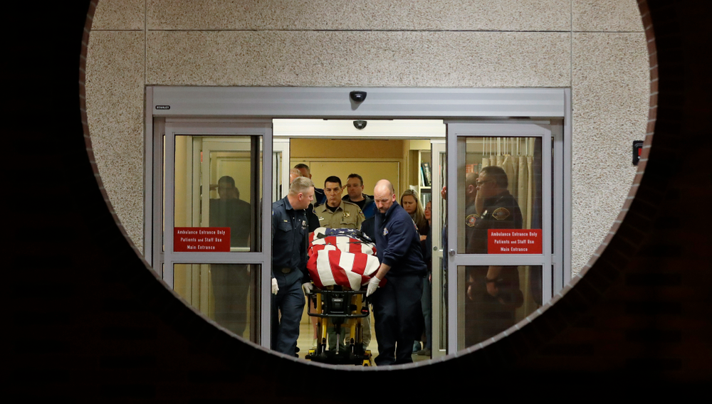 The body of a Kittitas County Sheriff's deputy is draped with a U.S. flag as it is carried out of Kittitas Valley Healthcare Hospital, in the early morning hours of Wednesday, March 20, 2019, in Ellensburg, Wash., as seen through a large circular entry window. A Kittitas County Sheriff's deputy was killed and a police officer was injured after an exchange of gunfire during an attempted traffic stop. (AP Photo/Ted S. Warren)