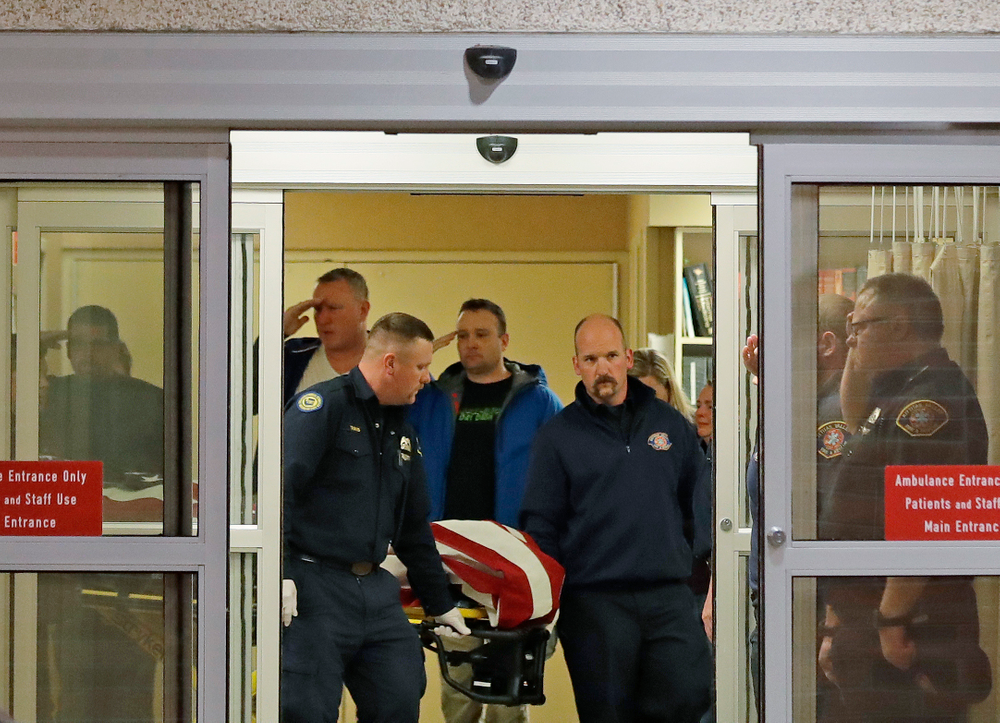 Fire and law enforcement officials join others in saluting as the body of a Kittitas County Sheriff's deputy draped with a U.S. flag is carried out of Kittitas Valley Healthcare Hospital, in the early morning hours of Wednesday, March 20, 2019, in Ellensburg, Wash. A Kittitas County Sheriff's deputy was killed and a police officer was injured after an exchange of gunfire during an attempted traffic stop. (AP Photo/Ted S. Warren)
