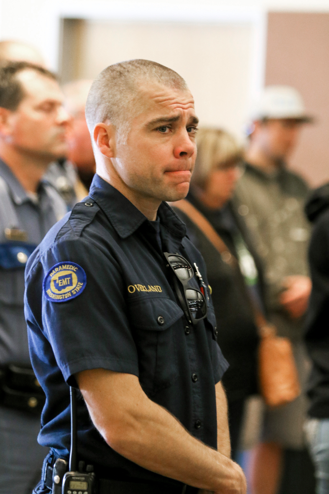 An EMT reacts while listening to Kittitas County Sheriff Gene Dana, not shown, speak at a news conference, Wednesday, March 20, 2019, in Ellensburg, Wash. about the death of Deputy Ryan Thompson, who was killed Tuesday evening when he and a Kittitas Police officer exchanged gunfire with a road-rage driving suspect in Kittitas, Wash. The driver of the vehicle was also shot and later died at a hospital. (Jake Green/The Daily Record via AP)