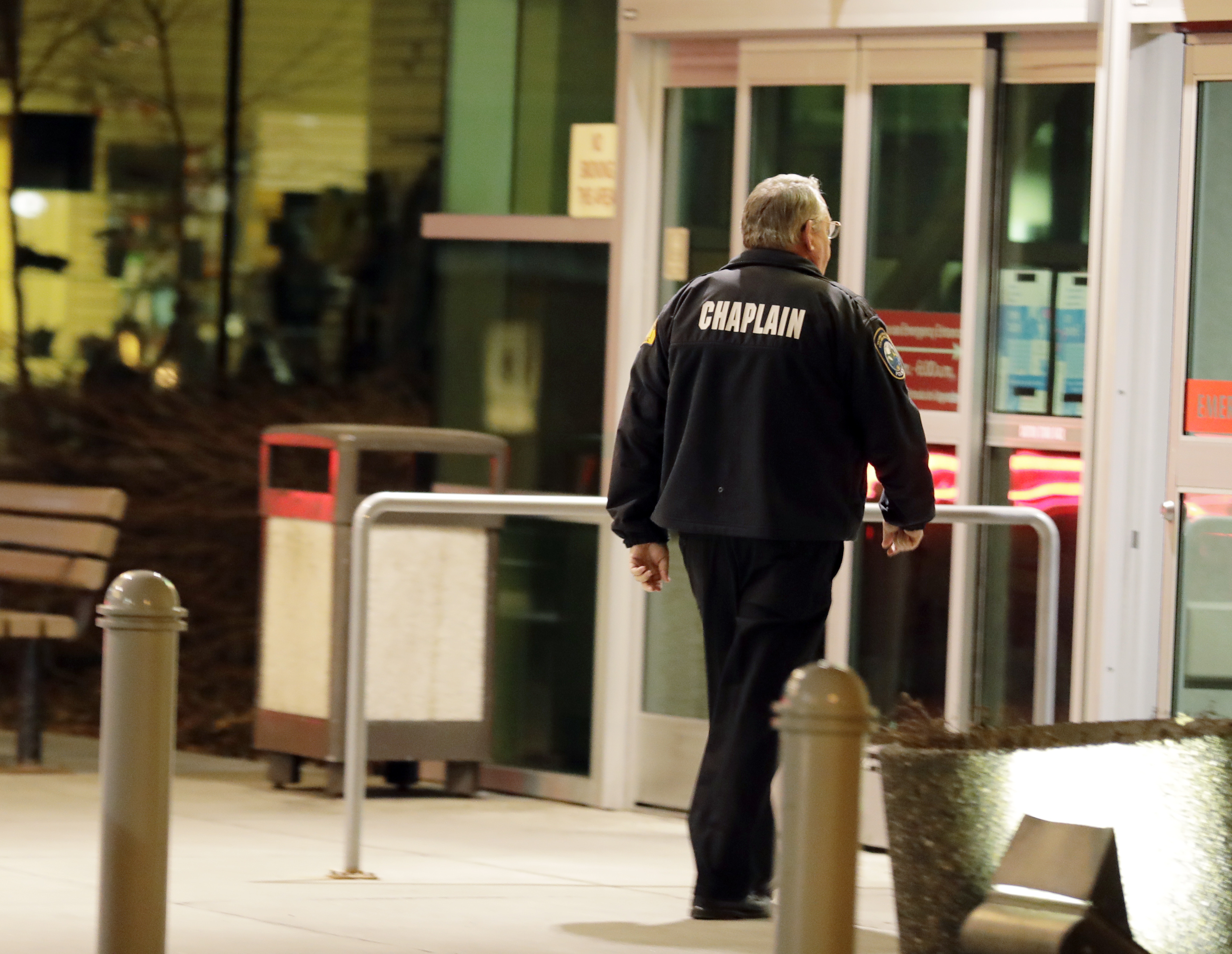 A law enforcement chaplain walks into Kittitas Valley Healthcare Hospital, in the late night hours of Tuesday, March 19, 2019, in Ellensburg, Wash., prior to a procession to accompany the body of a Kittitas County Sheriff's deputy away from the hospital. A Kittitas County Sheriff's deputy was killed and a police officer was injured after an exchange of gunfire during an attempted traffic stop. (AP Photo/Ted S. Warren)
