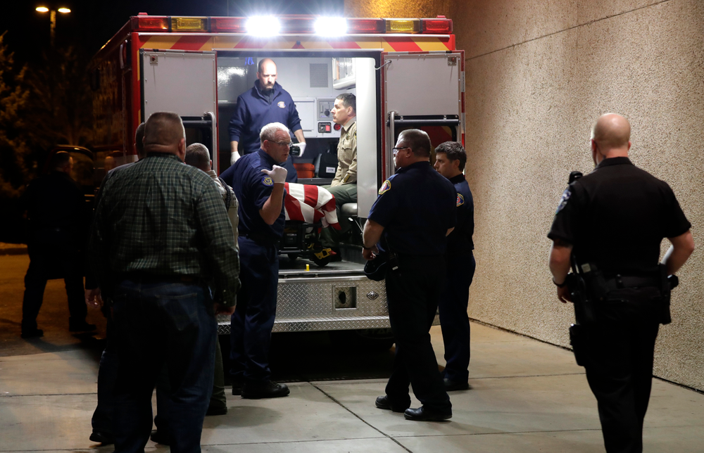 The body of a Kittitas County Sheriff's deputy is draped with a U.S. flag as it is loaded into an ambulance for a procession away from Kittitas Valley Healthcare Hospital, in the early morning hours of Wednesday, March 20, 2019, in Ellensburg, Wash. A Kittitas County Sheriff's deputy was killed and a police officer was injured after an exchange of gunfire during an attempted traffic stop. (AP Photo/Ted S. Warren)