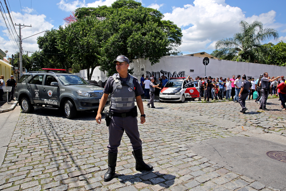 Police officers stand guard outside the Raul Brasil State School in Suzano, the greater Sao Paulo area, Brazil, Wednesday, March 13, 2019. The state government of Sao Paulo said two teenagers, armed with guns and wearing hoods, entered the school and began shooting at students. They then killed themselves, according to the statement. (AP Photo/Andre Penner)