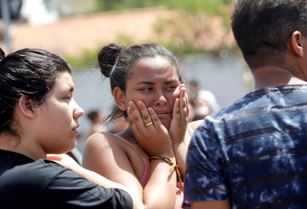 A student cries outside the Raul Brasil State School in Suzano, the greater Sao Paulo area, Brazil, Wednesday, March 13, 2019. The state government of Sao Paulo said two teenagers, armed with guns and wearing hoods, entered the school and began shooting at students. They then killed themselves, according to the statement. (AP Photo/Andre Penner)