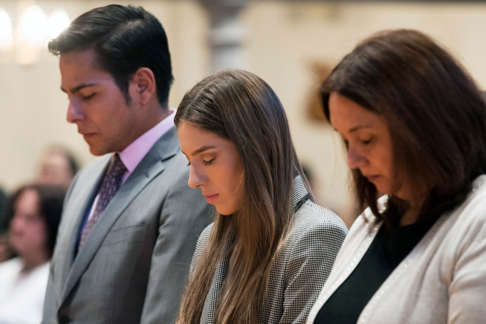 Fabiana Rosales, center, wife of Venezuelan opposition leader Juan Guaido, and Guaido supporter and activist Erick Rozo, left, pray while celebrating Mass at St. Teresa's Church on the Lower East Side of Manhattan, Tuesday, March 26, 2019, in New York. Rosales is emerging as a prominent figure in Guaido's campaign to bring change in the crisis-wracked country. (AP Photo/Mary Altaffer)