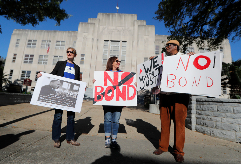 Wilfred Young, Agnes Courbille, left, and Karel Anne Zibe, center, of the St. Landry Parish branch of the NAACP, hold signs outside the St. Landry Parish courthouse during a bond hearing for Holden Matthews in Opelousas, La., Monday, April 15, 2019. Matthews, who is white, and is the son of a St. Landry Parish sheriff's deputy, was arrested Wednesday on three charges of arson of a religious building, and is the suspect in three recent arson fires that destroyed African American churches in Louisiana. (AP Photo/Gerald Herbert)
