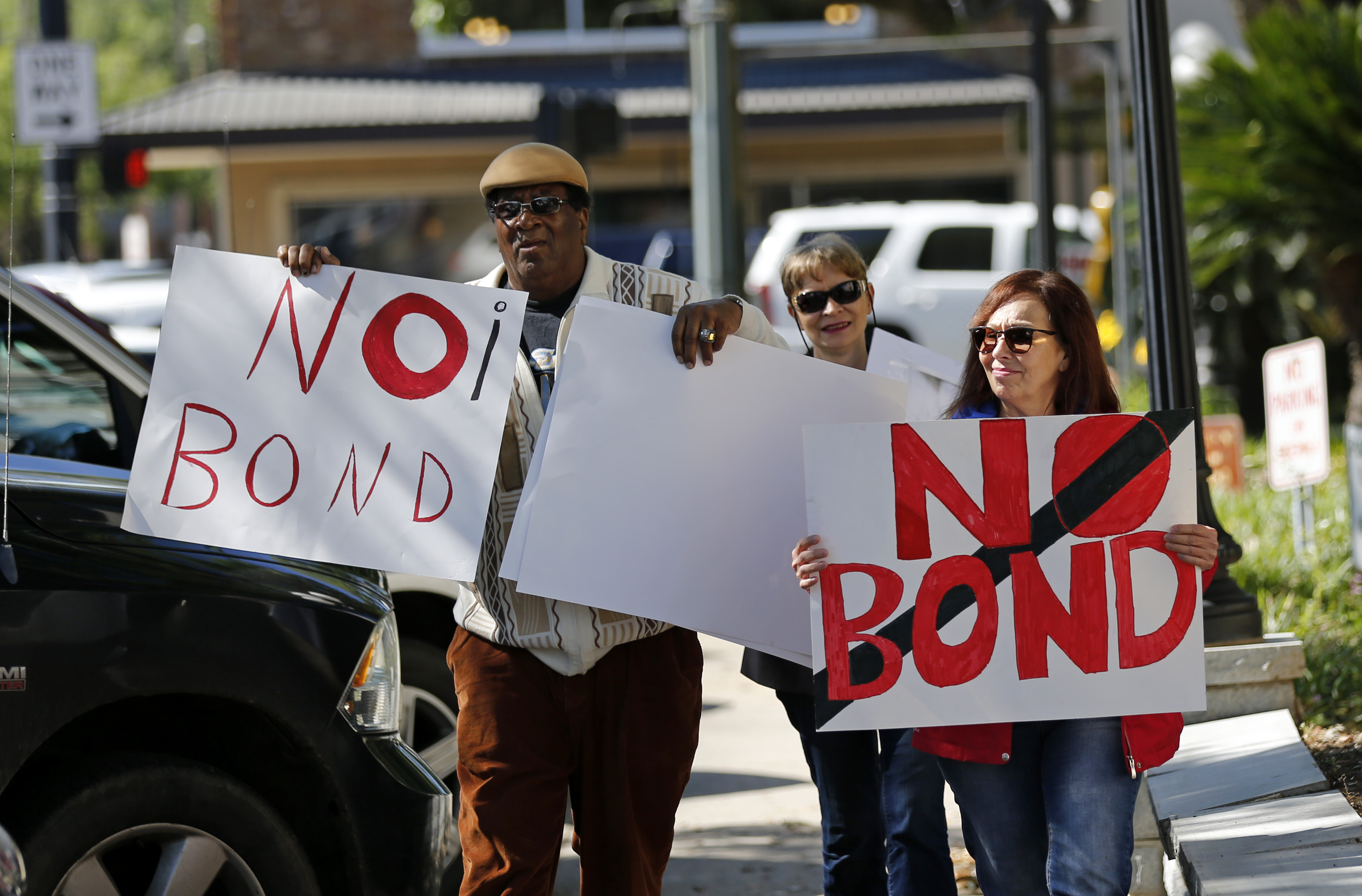 Wilfred Young, Agnes Courbille, center, and Karel Anne Zibe, right, of the St. Landry Parish branch of the NAACP, carry signs outside the St. Landry Parish courthouse after a bond hearing for Holden Matthews in Opelousas, La., Monday, April 15, 2019. Matthews, who is white, and is the son of a St. Landry Parish sheriff's deputy, was arrested Wednesday on three charges of arson of a religious building, and is the suspect in three recent arson fires that destroyed African American churches in Louisiana. (AP Photo/Gerald Herbert)